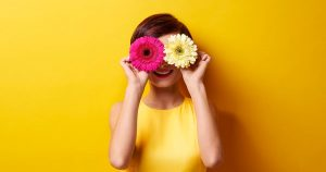 A woman is holding two flowers in front of her face