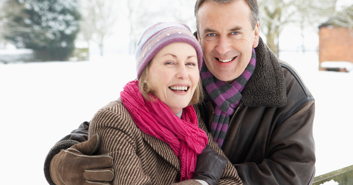 A man and woman are smiling in the snow