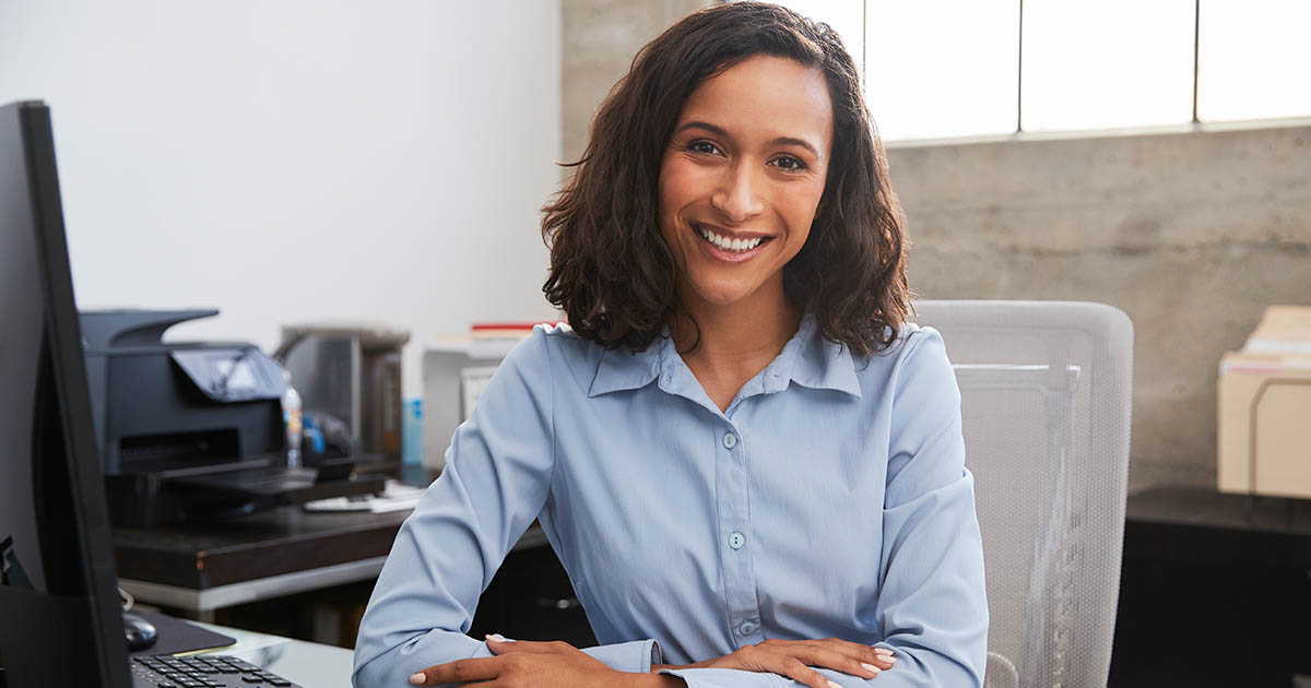 A woman is smiling at her work desk