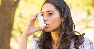 A woman is using an asthma inhaler