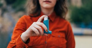 A woman is holding an inhaler