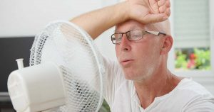 A hot man is sitting in front of a fan