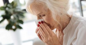 A woman is sneezing into a kleenex
