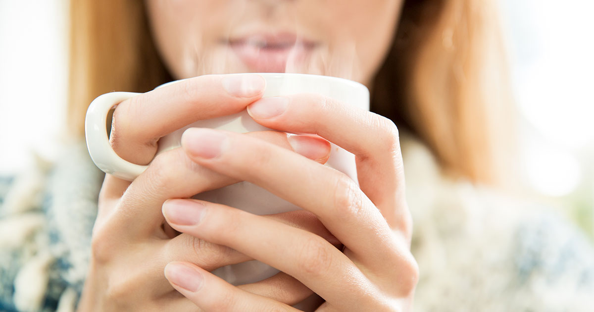 A woman is holding a steaming, hot cup with her hands