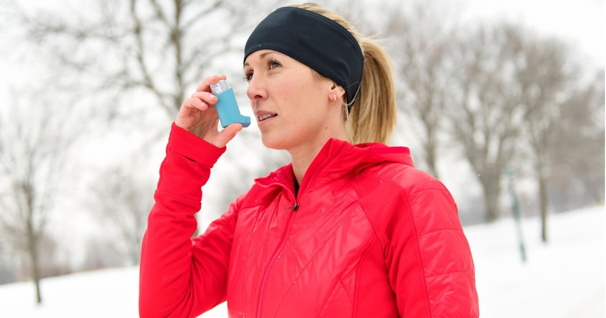 a woman with adult onset asthma holding an inhaler outside in winter