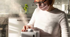 a woman using a humidifier in her home, to help with dryness, asthma and allergies
