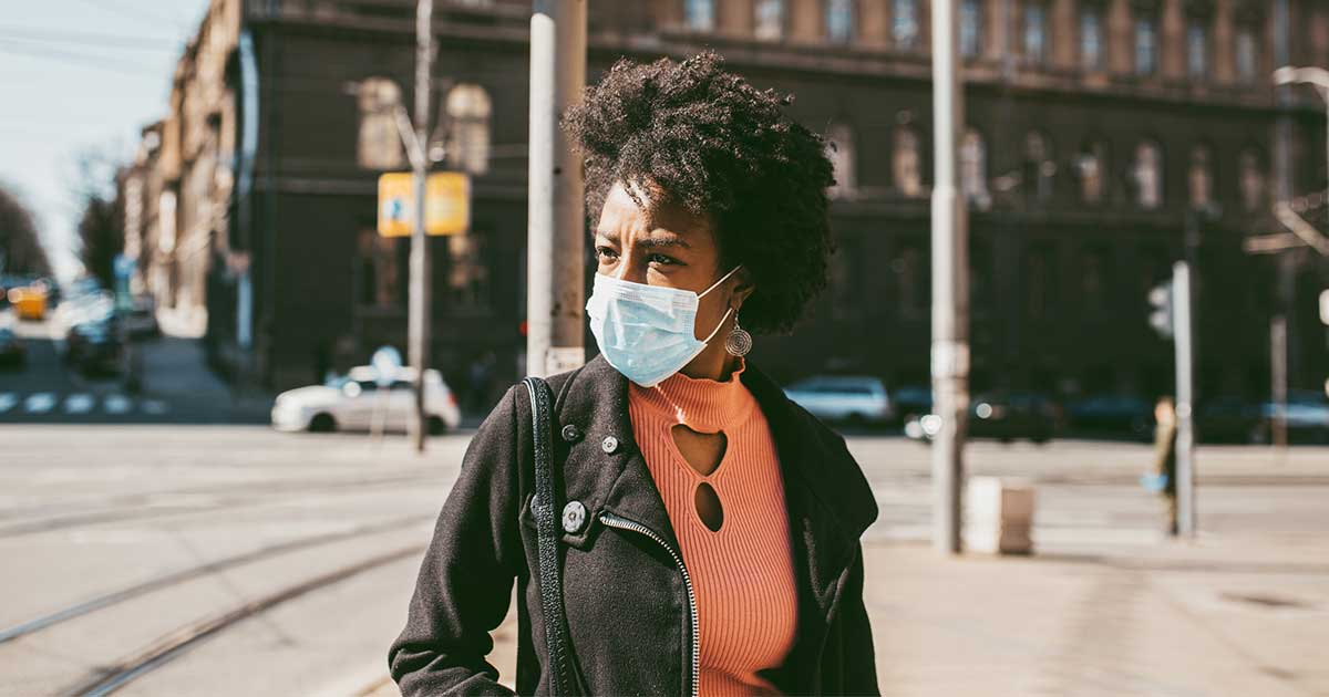 "a woman wearing a face mask or ""asthma mask"" in public"