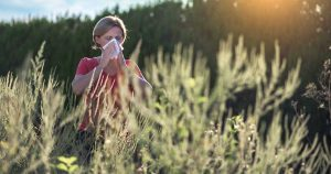 a woman with asthma and allergies sneezing in a field of ragweed